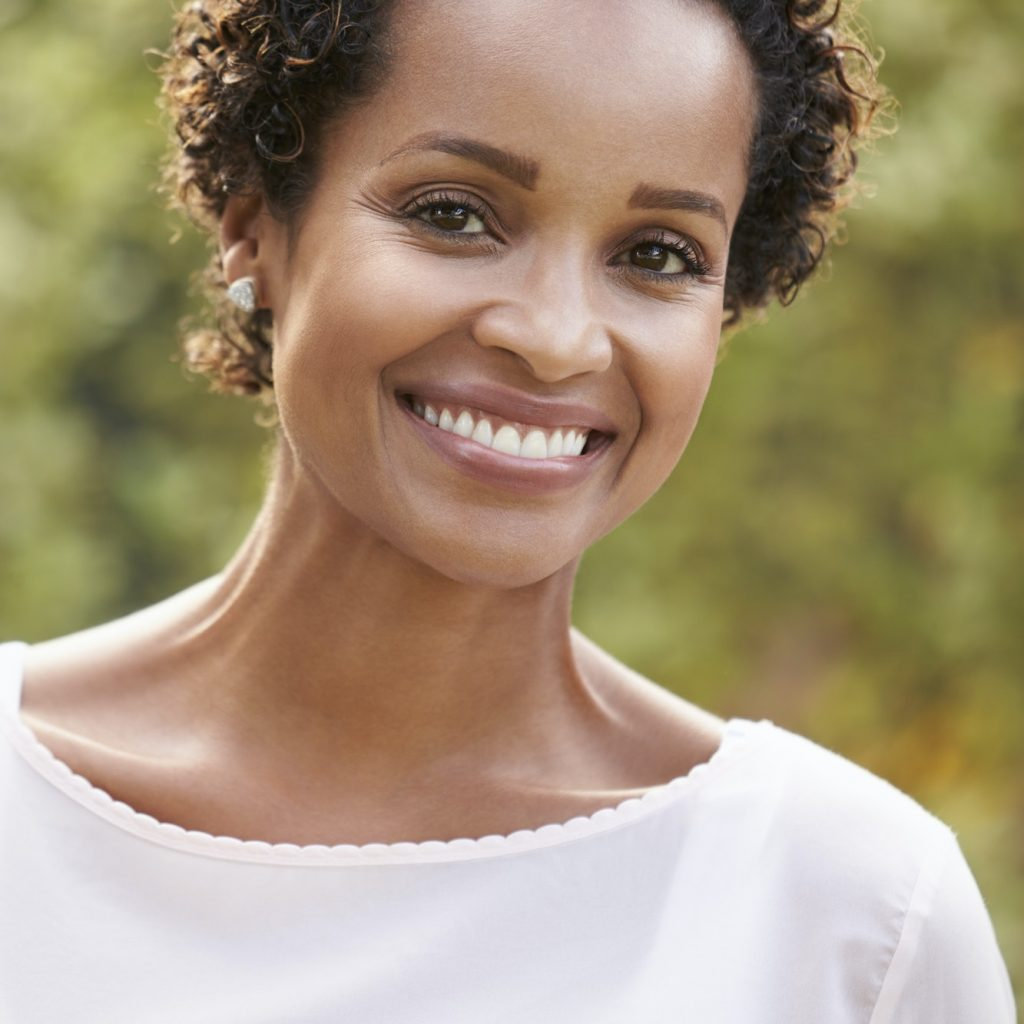 Young African American woman looks to camera, vertical